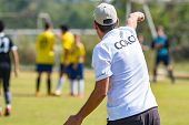 Back Of Football Coach Wearing White Coach Shirt At An Outdoor Sport Field Coaching His Team During  poster