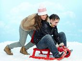 image of toboggan  - Portrait of happy couple tobogganing during winter vacation - JPG