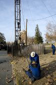 stock photo of roustabouts  - Workers tighten guy wires on oil well servicing rig - JPG