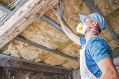 Old Roof Insulation. Caucasian Construction Worker In His 30s Inspecting Aged Roof And Mineral Wool  poster