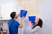 Young Woman And Repairman With Blue Bucket Collecting Water From Damaged Ceiling In Kitchen poster