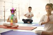 Little Girl With Chakra Points Practicing Zen Yoga In Group Indoors poster