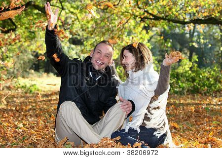 Happy Couple Playing With Autumn Leaves
