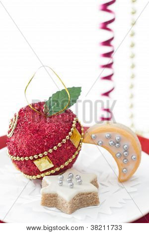 Single Christmas Decoration In Shape Of Red Apple With Couple Of  Cookies On White Background.