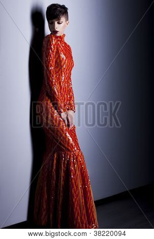 Pretty Fashion Woman In Elegant Long Red Dress Posing In Studio