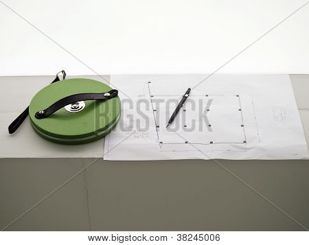 Measuring Tape And A Pencil Over A Construction Drawing