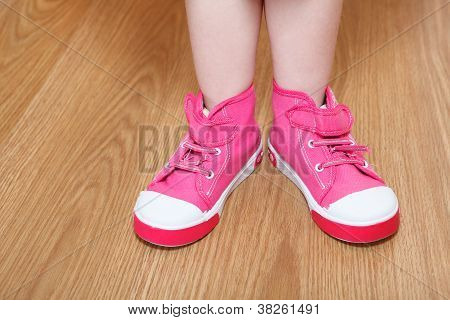 Children Legs In Pink Shoes Standing On The Floor