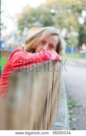 Young Woman Relaxation Leaning On A Fence And Put Head On Hands