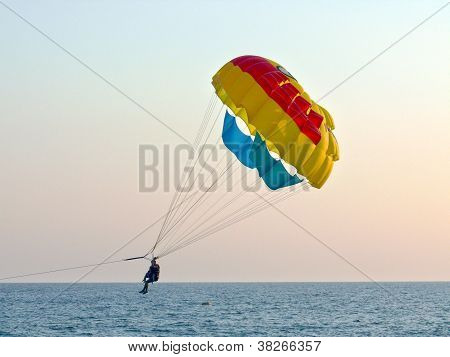 Tourists With Parachute Above The Sea