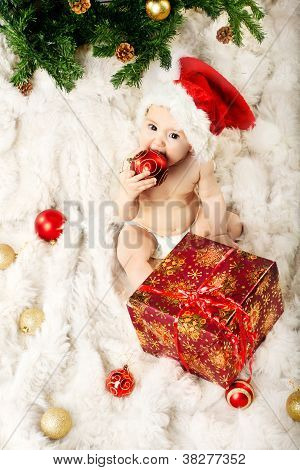 Christmas Baby In Red Hat Sitting On Fur And Eating Gift New Year Ball
