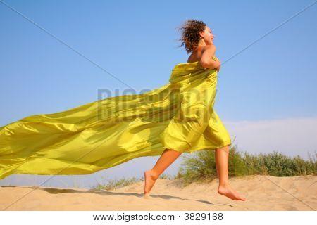 Young Girl Runs On Sand In Yellow Fabric Shawl