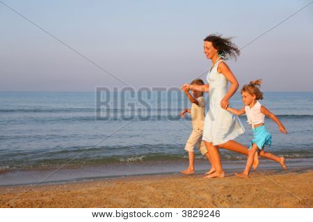 Mother With Children Running On Edge Of Sea