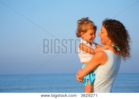 Mother Keeps Child At Hands Of Edge Of Sea