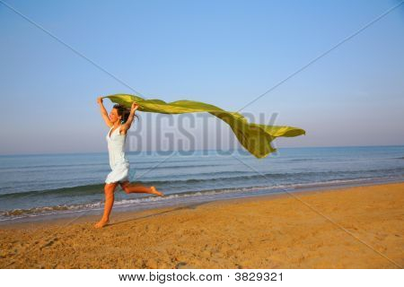 Young Girl Runs On Edge Of Sea With Shawl In Hands
