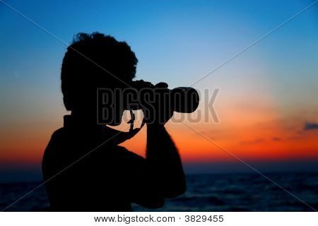 Silhouette Of Photographer Ashore On Sunset