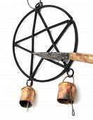 stock photo of pentacle  - Athame knife points to the back wrought iron pentacle star wind chime with rustic bells isolated on white - JPG