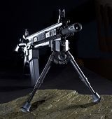 picture of ar-15  - Modern assault rifle with a bipod that is set up in the dark - JPG