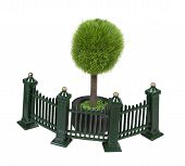 picture of scrollwork  - Metal fence with scrollwork painted green in front of a potted tree - JPG