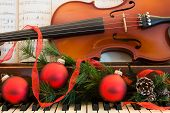 stock photo of violin  - A violin and sheet music sits on a piano that has been decorated for the Christmas holiday - JPG