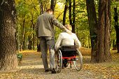 foto of disabled person  - Husband and handicapped wife taking stroll in park alley in fall time - JPG