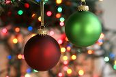 stock photo of christmas ornament  - Frosted green and red Christmas ornaments hanging in front of blurred Christmas lights - JPG