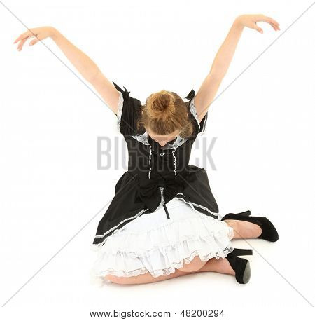Caucasian Girl Child Sitting in Marionette Pose in Lolita Fashion Dress. Arm up, head down.