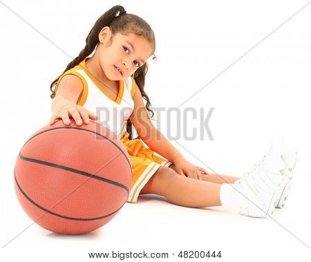 Beautiful Hispanic preschool girl with basketball in uniform. clipping path