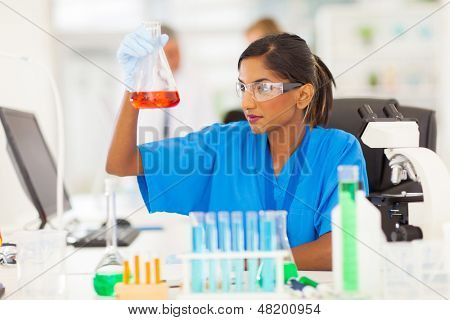 beautiful young indian medical researcher analyzing liquid in a flask