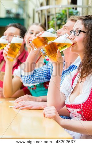 Friends in traditional Bavarian Tracht in restaurant or pub with beer in Bavaria, Germany