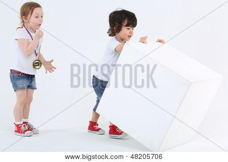 Little girl with medal on chest admiring looks at boy reversing large cube on white background.