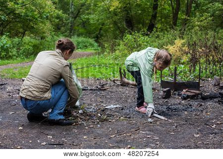 Mother and daughter helping clean up the forest in Elk Island National Park.