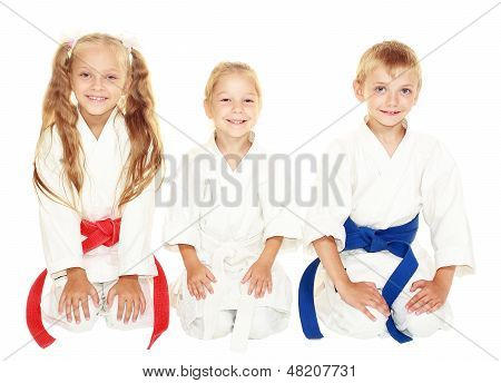 Young children with a smile in kimono sitting in a ritual pose karate