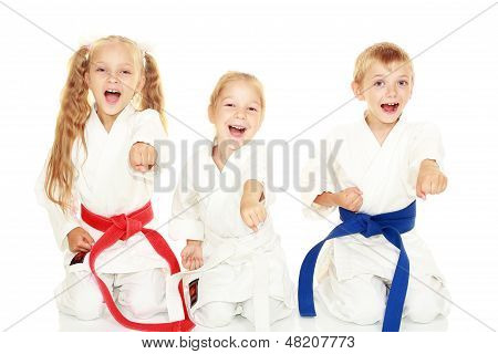 Young children with a smile in kimono sitting in a ritual pose karate punch arm