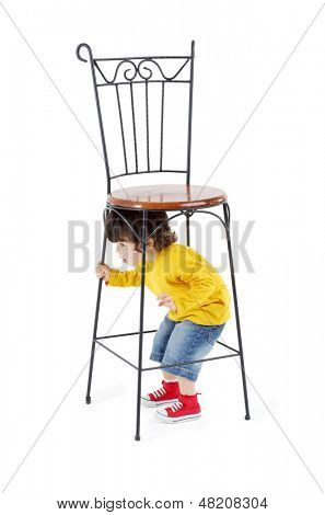 Little boy hides under high wrought-iron chair isolated on white background.