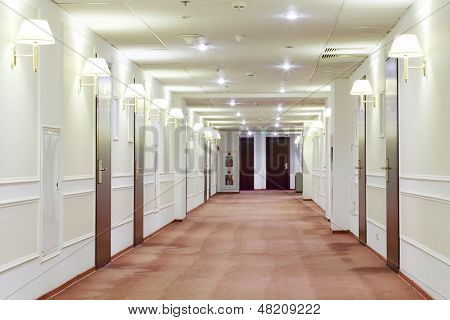 Spacious light hallway with many doors leading into hotel rooms.