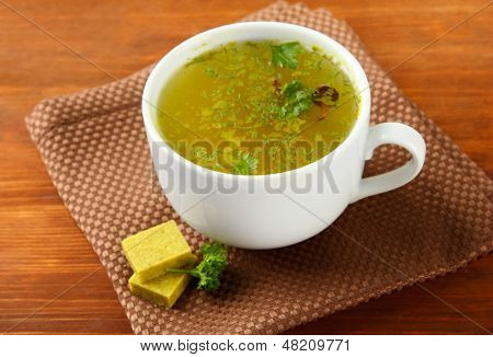 Cup of soup with bouillon cubes on wooden background