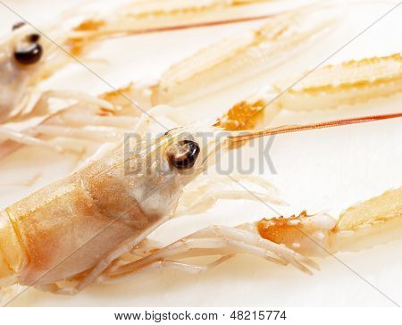 Two Langoustines On A White Cutting Board