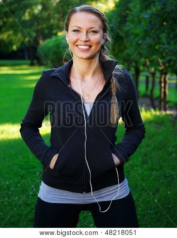 Young beautiful sporty brunette woman in a park with earphones