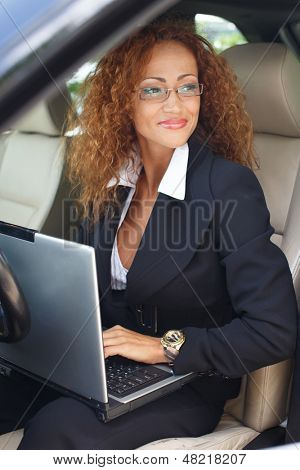 Beautiful middle-aged redhead businesswoman in black jacket with laptop behind steering wheel