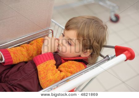 Little Girl In Shop Lies In Cart And Holds Finger In Mouth