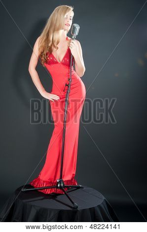 Portrait Of A Beautiful Blonde Woman In Red Dress And Black Gloves With A Retro Microphone