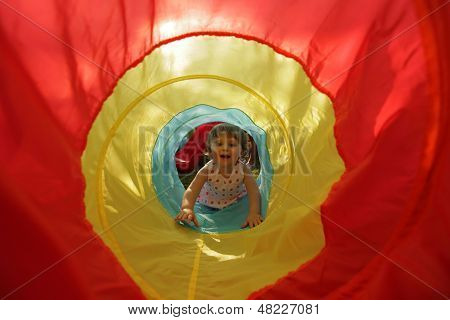 Little girl in a toy tunnel