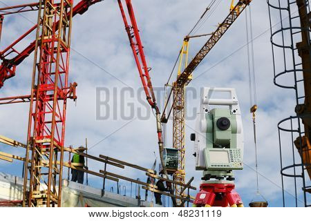 surveying measuring instrument inside construction plant, cranes and scaffolding
