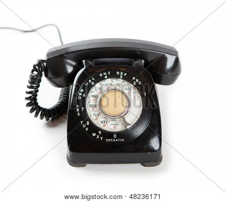 Old Late 60s - 70s style black telephone with rotary dial. Isolated on white.