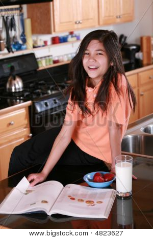 Child Sitting On Countertop Holding Glass Of Milk