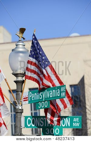 Washington DC, Pennsylvania Avenue and Constitution Avenue junction street signs with United States of America flag on same post