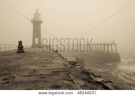 Whitby East pier and Lighthouse in thick fog