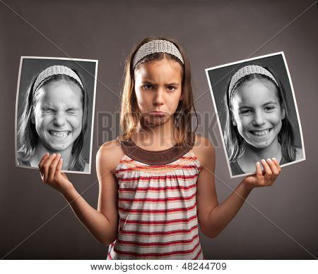 portrait of sad little girl holding two photos of herself with happy expression
