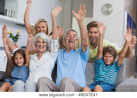 Multi-generation family raising their arms together in the living room