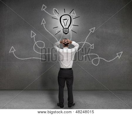 Stressed businessman looking at a light bulb drawn on a light bulb